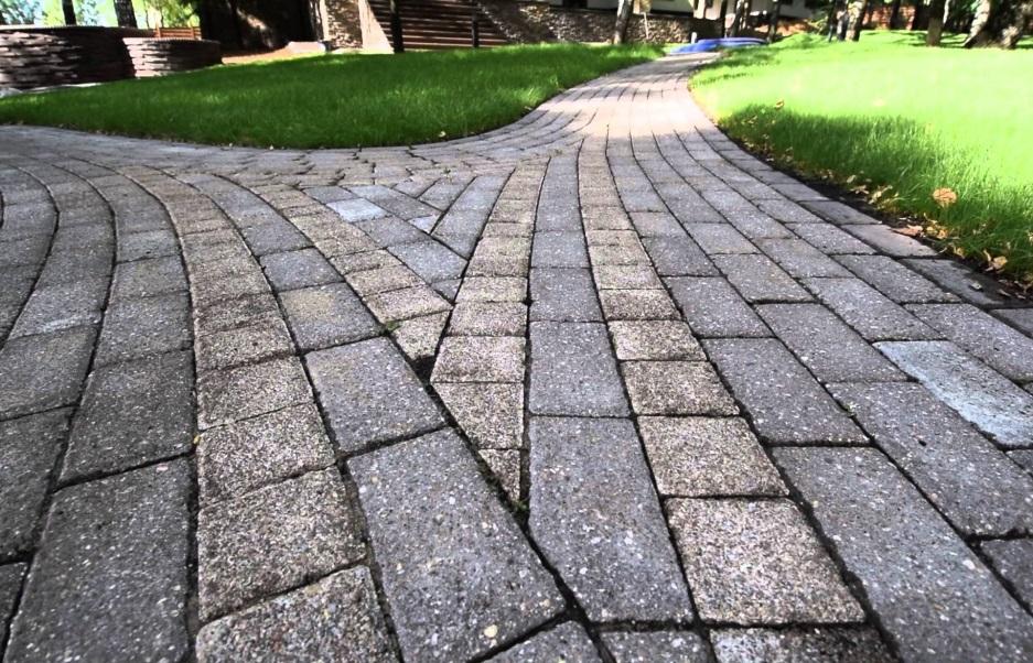 Серая тротуарная плитка в сочетании с газонной травой выглядит привлекательно