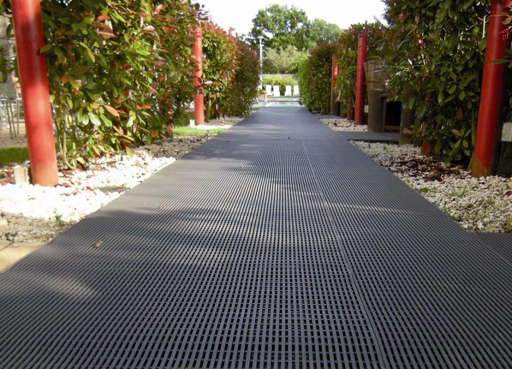 Высокопрочные плиты из черного пластика используются для сооружения главной дороги к дому