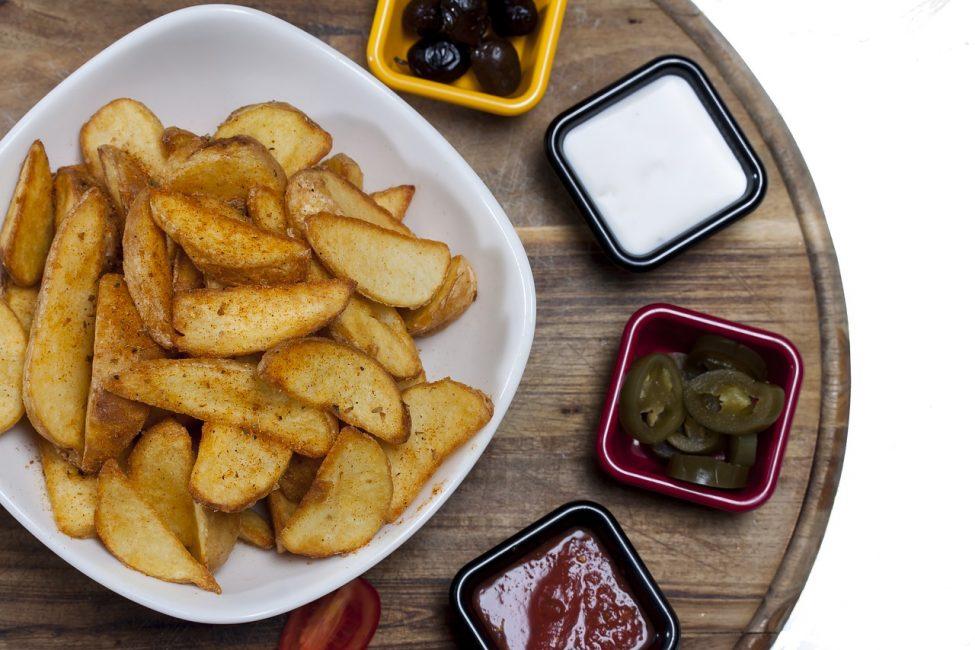 картошка большими дольками на тарелке с соусами
