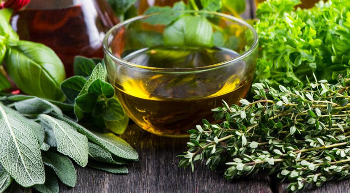 Оливковое масло в окружении итальянских трав: розмарина, тимьяна, орегано.