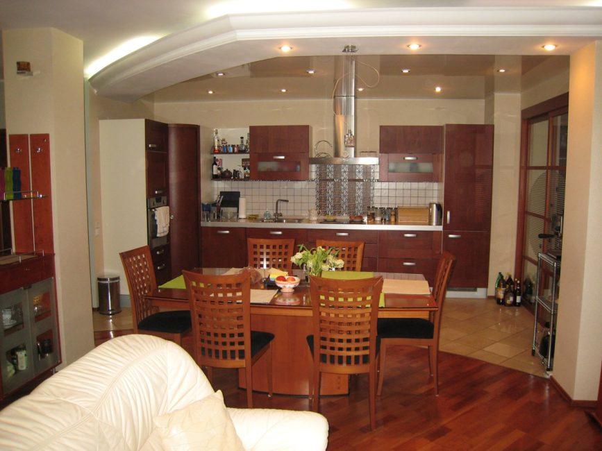 Зонирование пространства кухни-гостиной при помощи стола, потолка и напольного покрытия