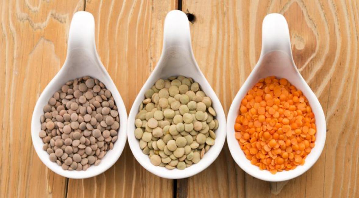 Зерна чечевицы разных сортов, среди которых также находится красный представитель бобовых.
