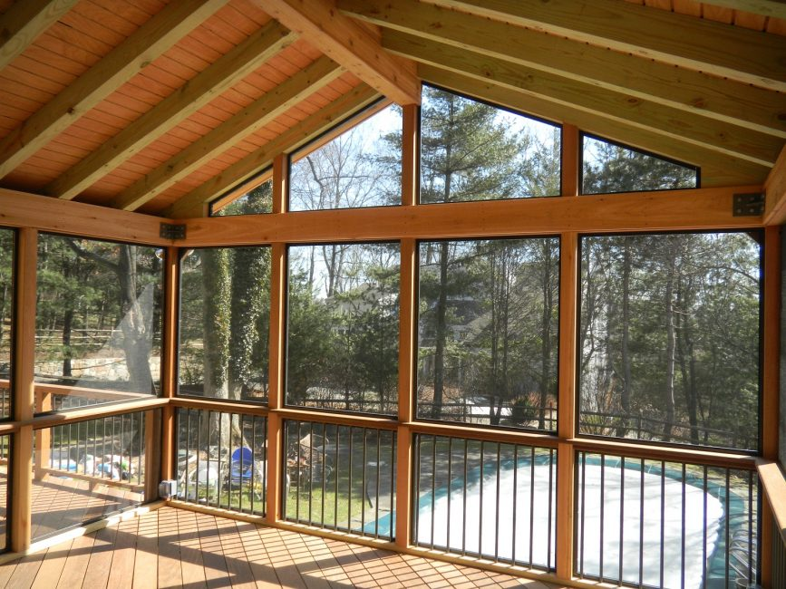 Массивные потолочные балки в стиле кантри вполне сочетаются с современными стеклопакетами, изготовленными под дерево