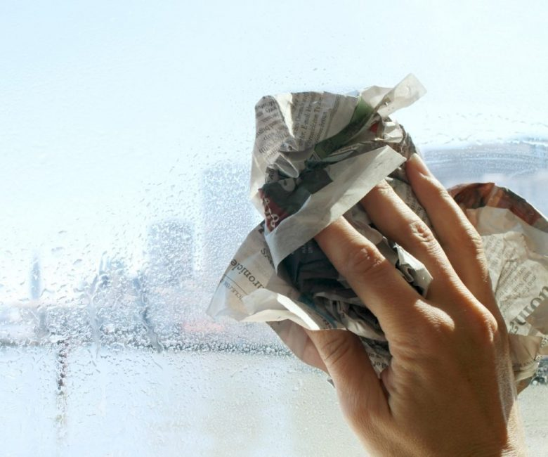Мытье окна с помощью газеты