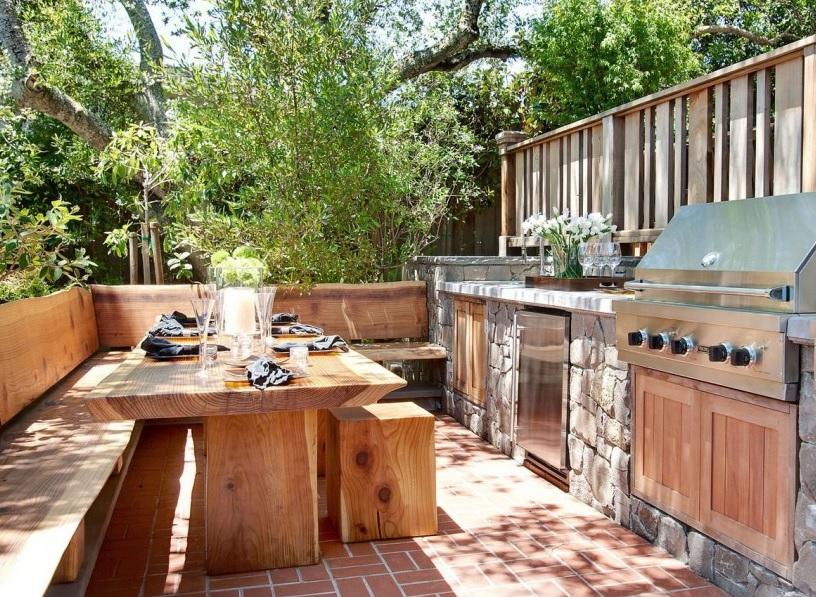 Расположить летнюю кухню лучше в тени деревьев, которые защитят ее как от жары, так и пронизывающих ветров