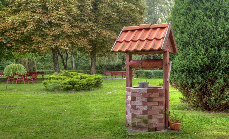 Декоративный колодец на даче с оголовком из кирпича