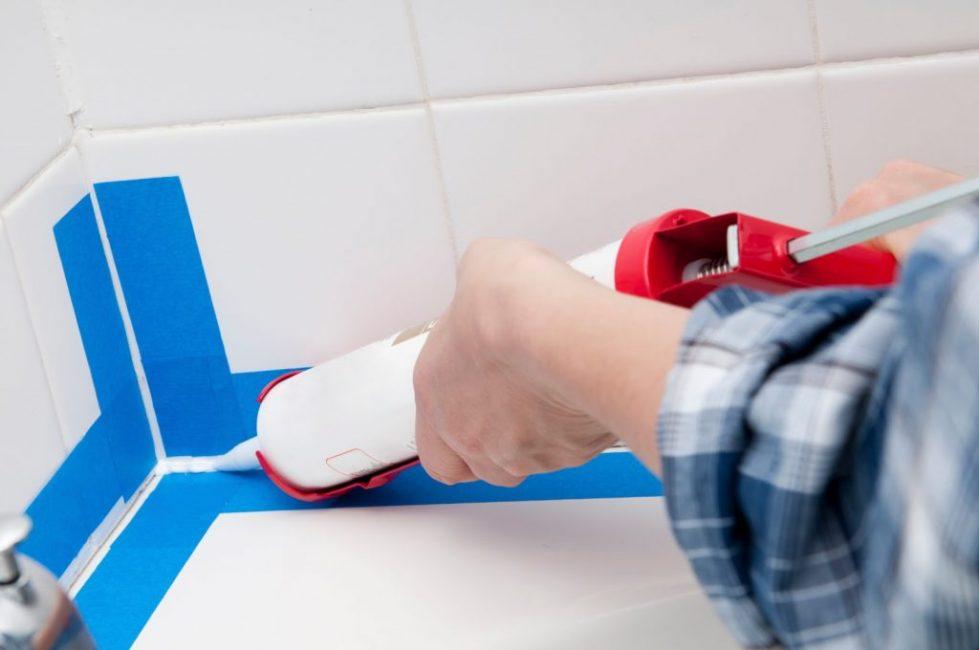 Чтобы герметизирующий шов был ровным, на стены и бортики ванной клеят малярный скотч