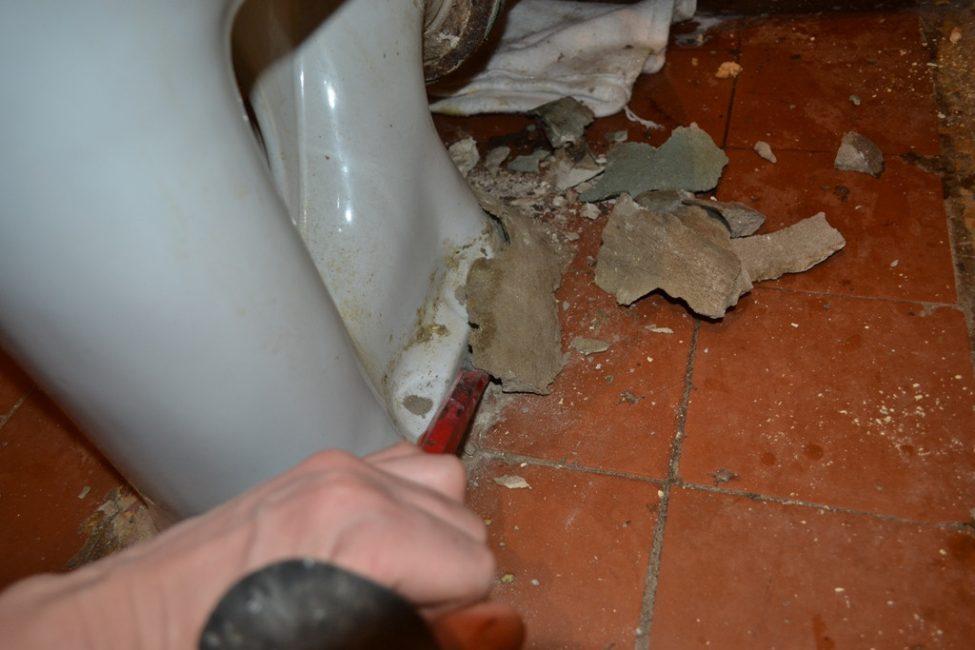 Цементную обмазку с подошвы чаши сбивают молотком и зубилом