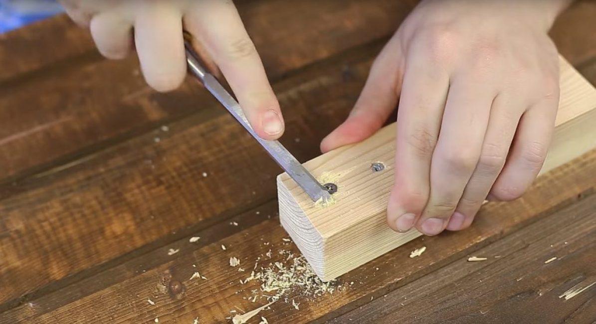 При помощи стамески или долота обрабатывается деревянная поверхность, находящаяся в районе шляпки шурупа