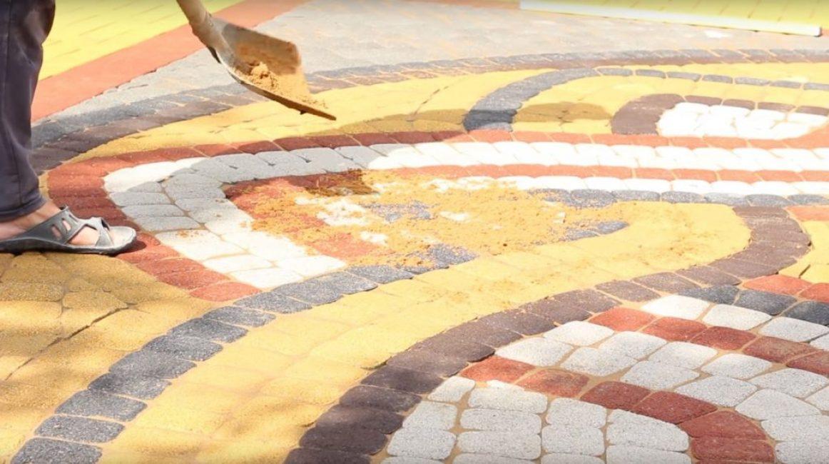 Песок насыпают небольшим слоем сверху уложенной плитки