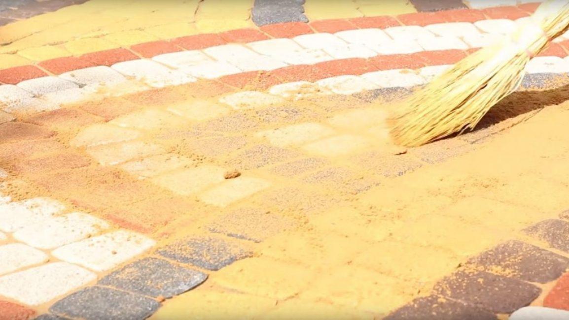 Далее песок равномерно распределяют по поверхности при помощи обычного веника