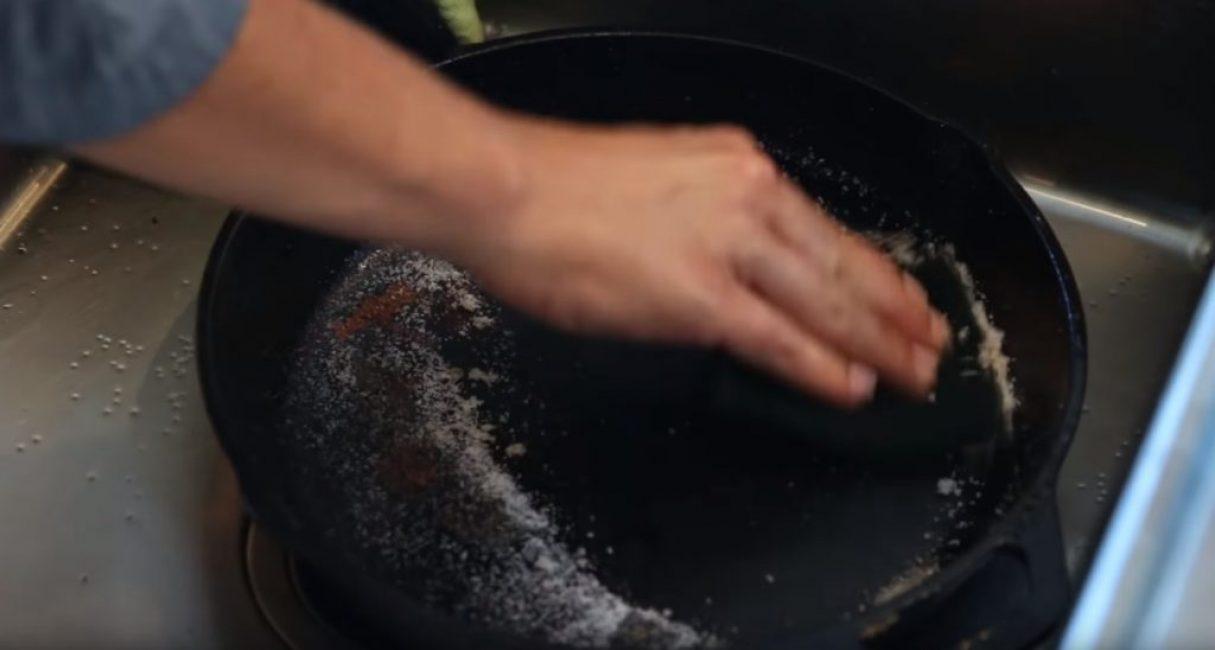 Очистка дна сковороды спонжем и солью