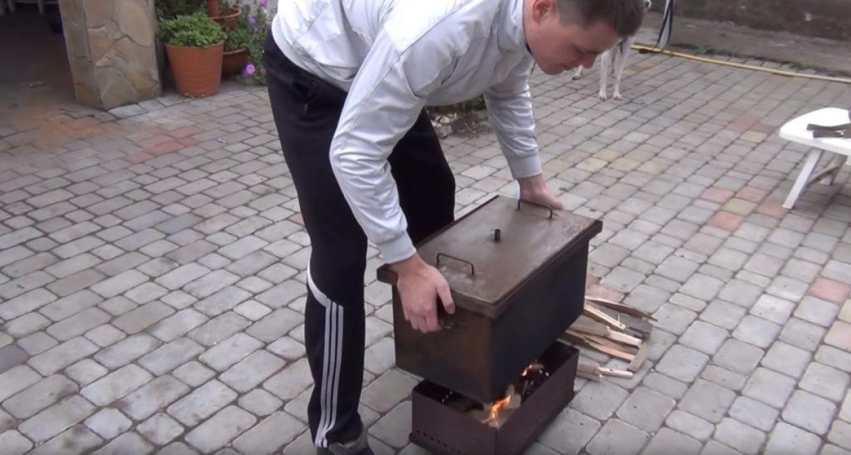 После того, как огонь разгорится, коптильню устанавливают на источник тепла