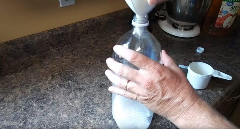 При помощи воронки в бутылку насыпают 100-150 г сахара