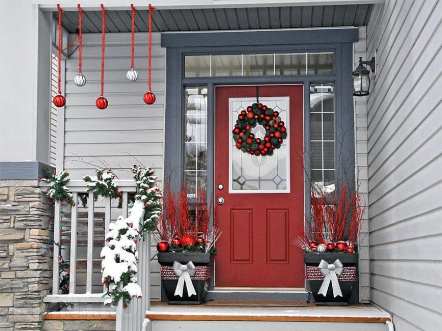 На дверь вешают классический венок из еловых веток и шариков