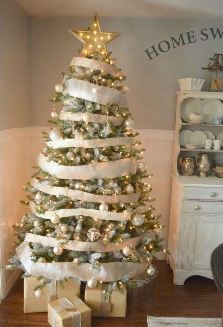 Здесь в центре внимания декор из белых и золотистых лент, которые щедро окутывают елочку по кругу