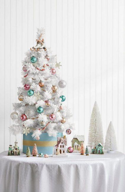 Входную зону дома можно оформить с юмором! Маленькое белое дерево с красными лентами и шишками обязательно вызовет улыбку