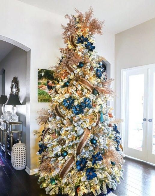 4 Королевская елка в сине-золотой гамме, где акцент сделан не на игрушках, а на цветах и лентах