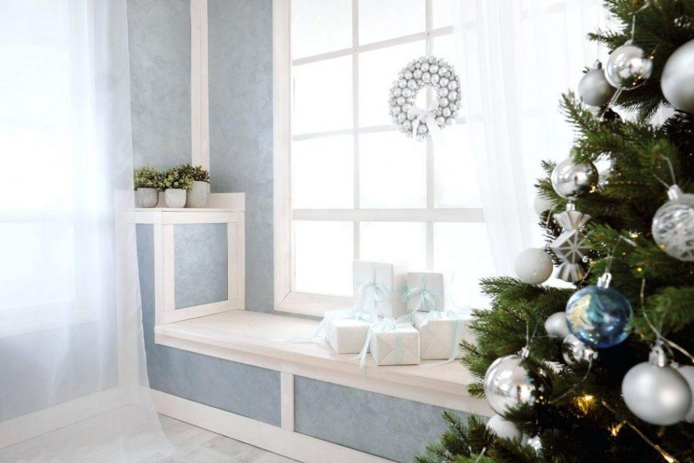 Если рядом с окном стоит праздничная елка, орнаменты и украшения одного оттенка для создания единого стиля