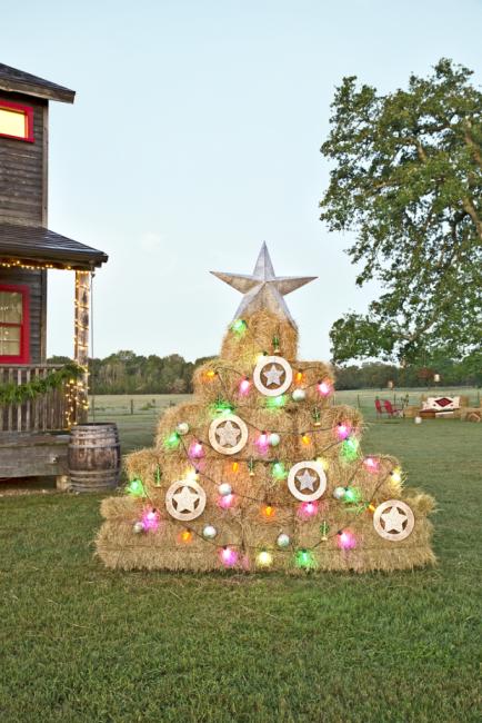 На улице тоже можно устроить праздник. Импровизированная елка из тюков соломы декорированная гирляндой из лампочек – одна из классных идей!