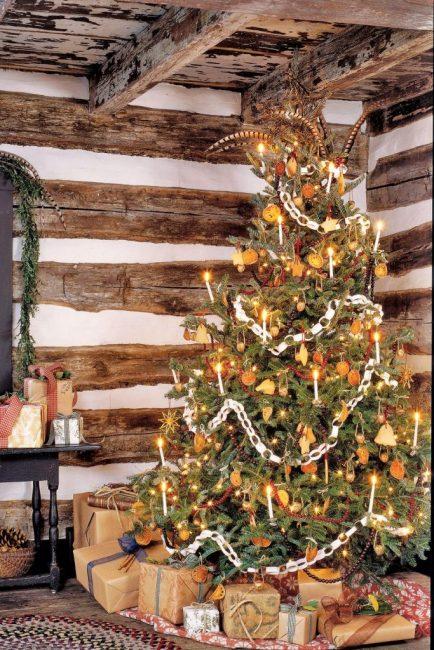 Декор в колониальном стиле. Он создан сушеной айвой, цепочкой из бумаги, печеньем и крохотными подарочками на елке