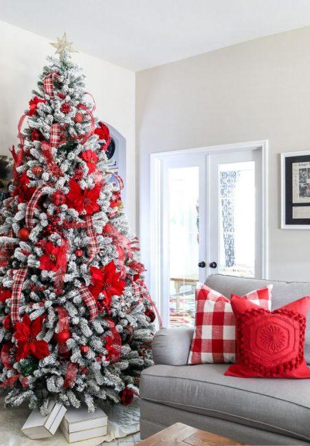 Декор ели может по цвету сочетаться с текстилем. В этом интерьере доминирует красный