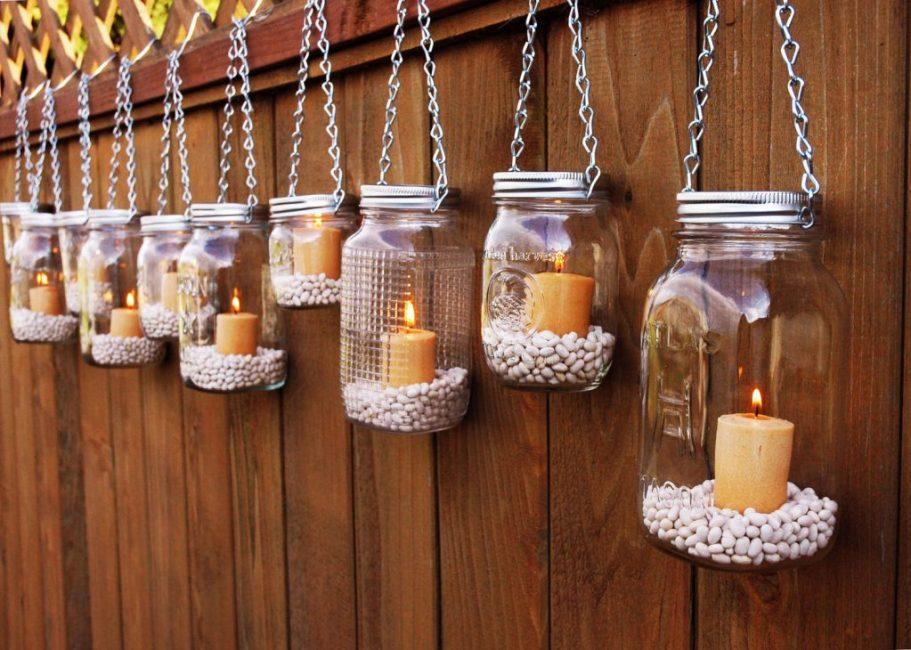 Подсвечники можно повесить вдоль садового забора, чтобы холодные вечера были теплее
