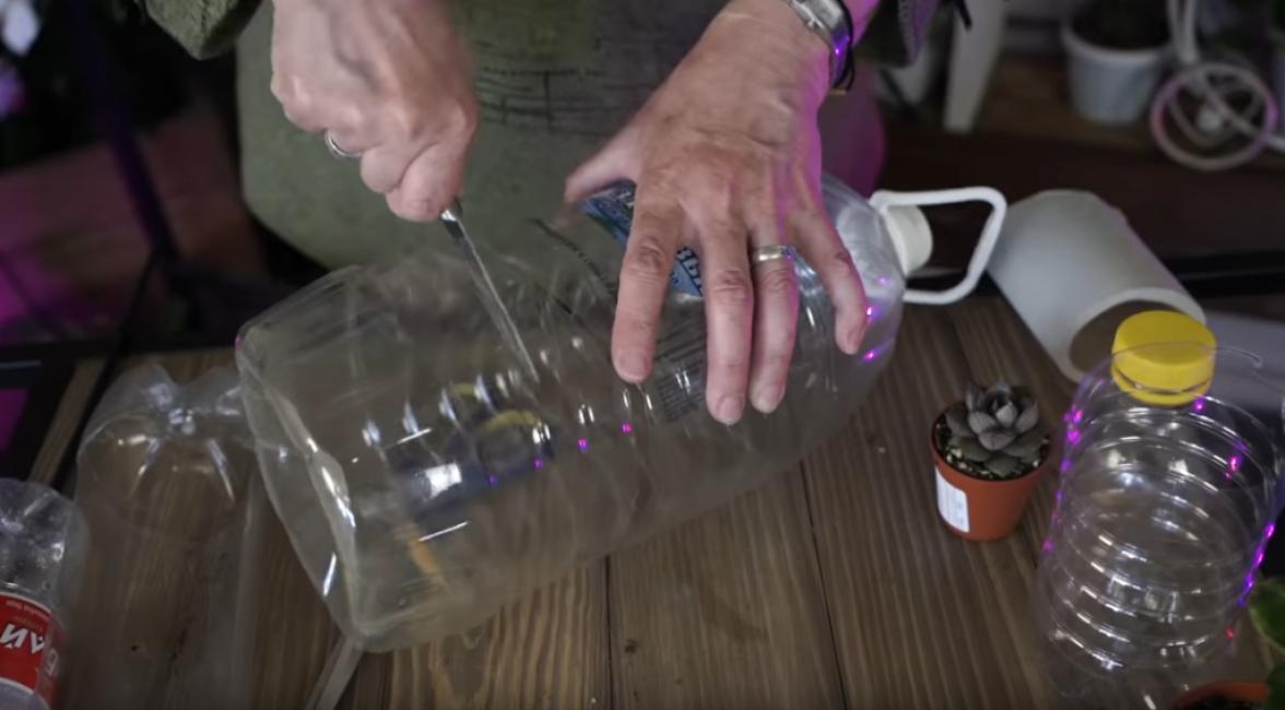 Большую пластиковую бутылку с ручкой и крышкой разрезаем на две половины при помощи острого ножа.