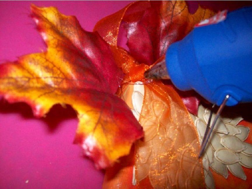 В углу картины приклеивают ленту из органзы и декоративный кленовый лист