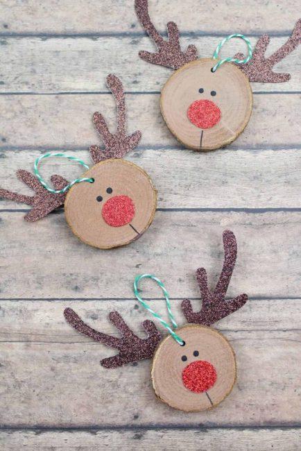 Олени – символ Рождества, помощники Санта Клауса. Если к спилу приклеить вырезанные из картона рога, нос и глазки – получится милая оленья морда. Главное – использовать блестящий картон!
