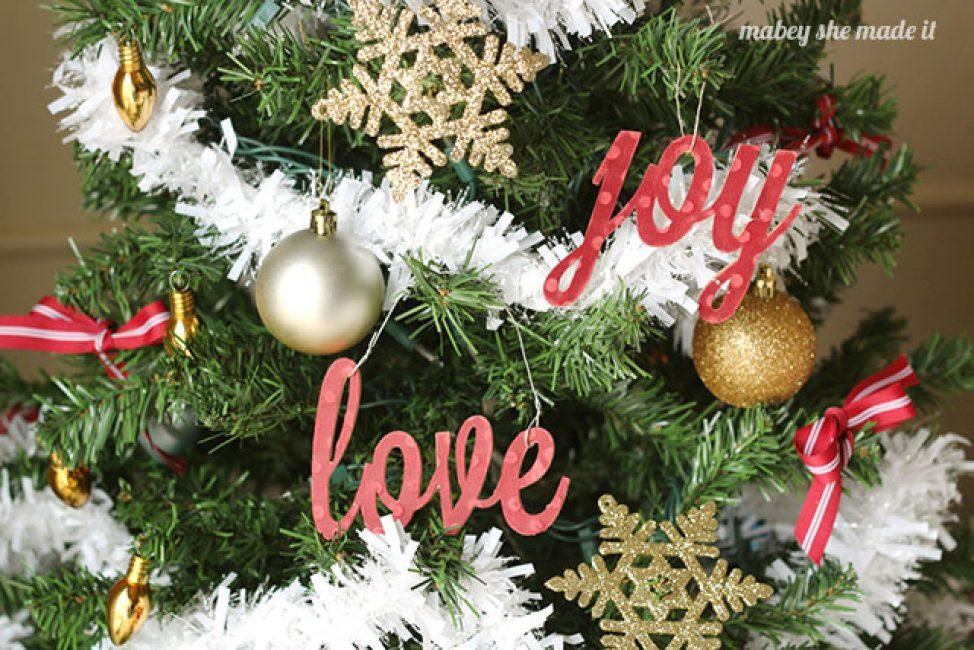 Ель в Новый год может украшать не только игрушка, но и надписи. Вырежьте слова из цветного картона, создайте из них поздравления и необычный декор готов!