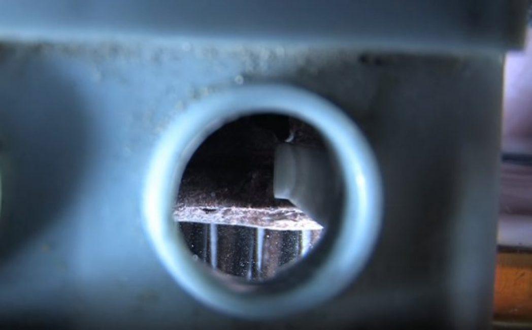 При помощи фонарика можно увидеть внутри аккумулятора сульфатацию — белый налет на пластинках.