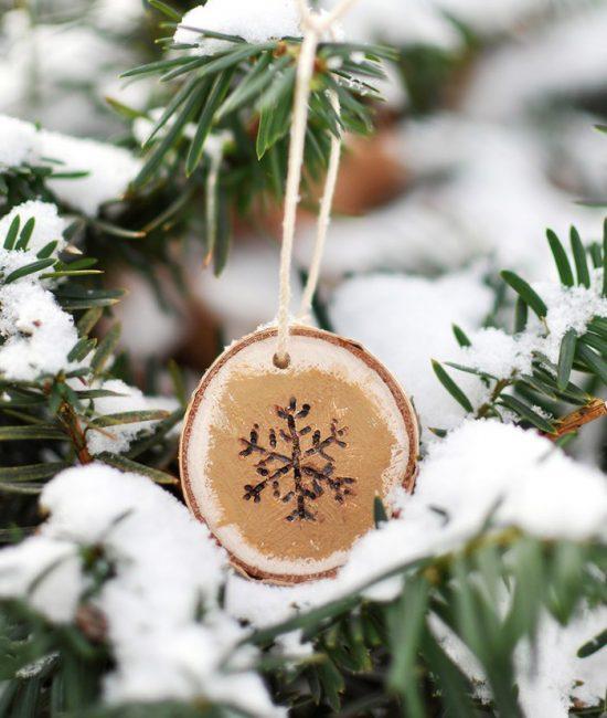 Снежинка на спиле – очень мило. Ее несложно сделать с помощью газовой горелки или просто нарисовать акрилом. Для достижения объемного изображения края снежинки подкрашивают золотом. Украшение в деревенском стиле готово, осталось только подвесить его с помощью шпагата на еловую ветку