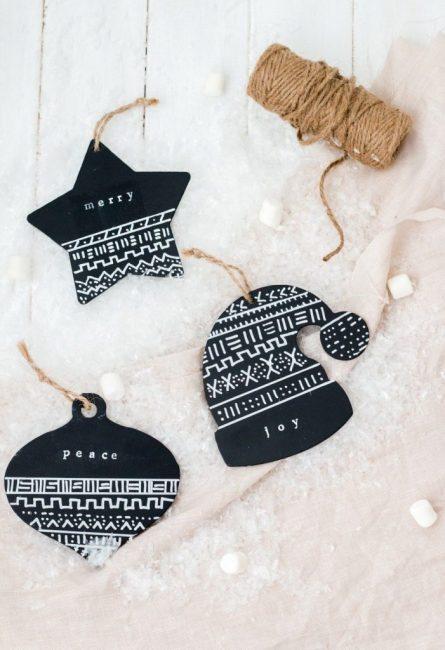 Украшения из плотной черной глянцевой бумаги выглядят очень брутально. Из нее можно вырезать любые формы в новогодней тематике и нанести орнаменты белой краской. В качестве подвеса – экологичный джутовый шпагат