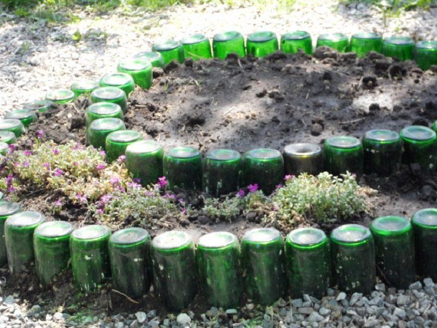 Бордюр клумбы из стеклянных бутылок зелёного цвета
