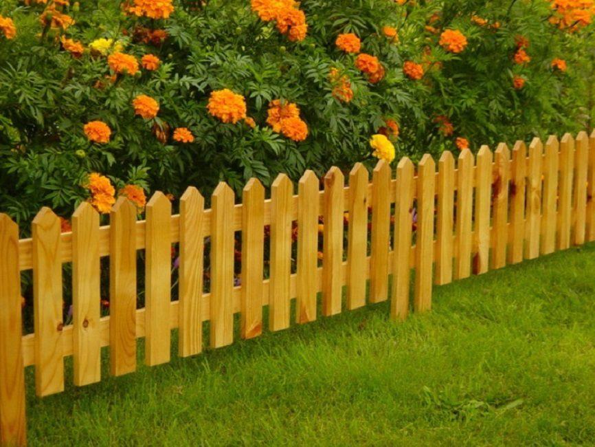Самое простое деревянное ограждение для клумбы – классический штакетник