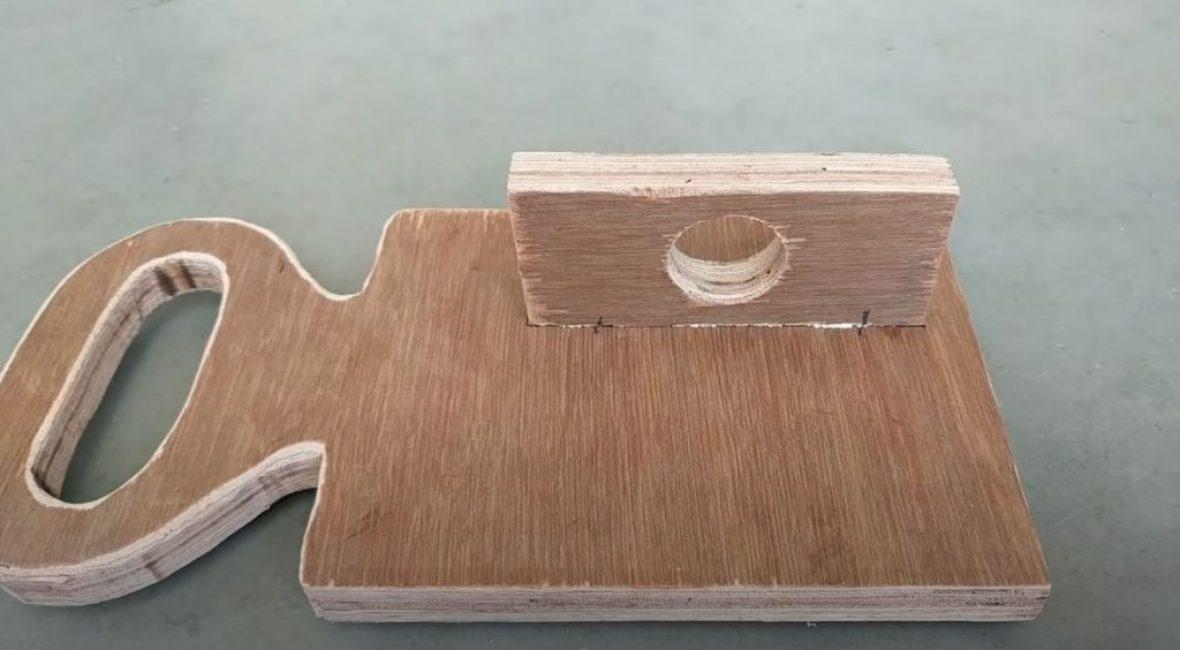вырезаем из толстой фанеры небольшой прямоугольник и просверливаем в нем отверстие под патрон дрели